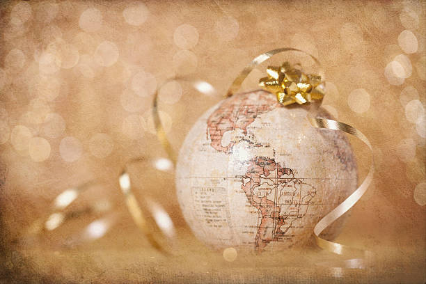 Christmas World Globe Ornament with Ribbon on Defocused Textured Background